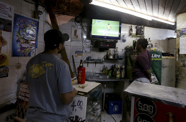 Men watch the opening soccer match of the Confederations Cup between Brazil and Japan on television at a bar in the Santa Marta slum of Rio de Janeiro