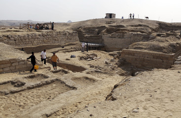 Archaeologists and workers are pictured at the site of a recently discovered complex of tombs in the Abusir region