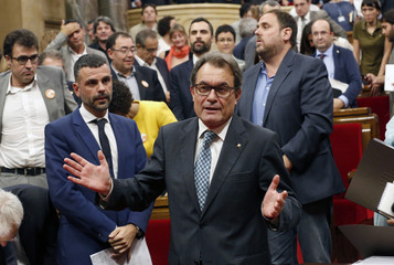 Catalonia's President Mas gestures to photographers after Catalonia's Parliament  approved a regional consultation law in Barcelona