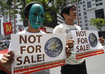 Members of the Freedom from Debt Coalition display placards while holding a protest in front of the UN office in Manila