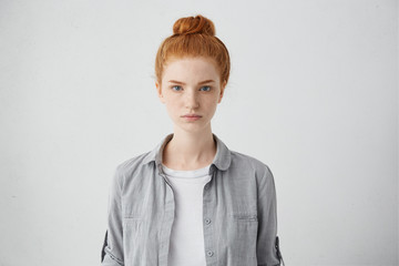 Waist up portrait of beautiful European 20 y.o. woman with freckles and hair knot posing isolated against grey studio wall background with copy space for your text, having calm expression on her face