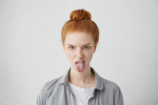 Headshot of naughty girl of European appearance sticking out tongue, trying to tease someone, looking immature and offensive, all her appearance expressing rudeness and disgust. Signs, symbols