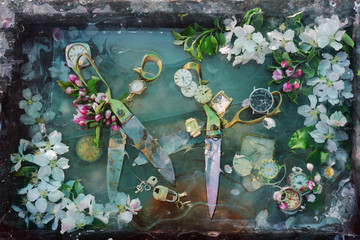 Art still life with two pairs of bright shiny metal scissors very old wrinkled flowers among spring white flowers of apple trees in water, original design for interior decoration.