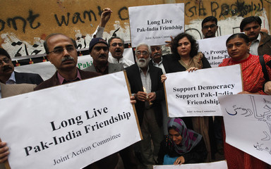 Members of Joint Action Committee (JAC) an alliance of civil society organizations hold placards while observing the global vigil for peace between India and Pakistan, in Karachi