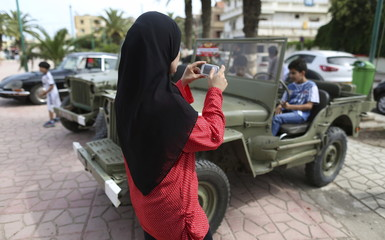 A woman photographs her children as they sit in a vintage car displayed during an exhibition in Rouiba, on the outskirt of Algiers