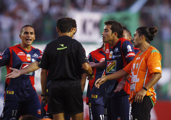 Damian Alderete and Jorge Hernandez of Mexico's Monarcas Morelia argues with referee Antonio Arias during their Copa Libertadores soccer match against Argentina's Banfield in Buenos Aires