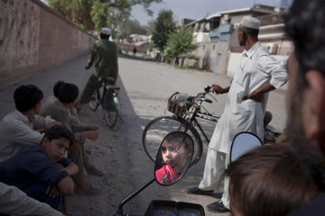 A boy is reflected in a side mirror of a motorcycle as residents wait to return to their homes in Peshawar
