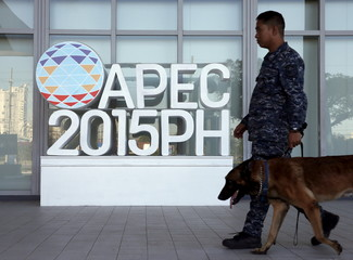 A military personnel walks past an APEC logo with his sniffer dog at the media center of the APEC summit in the capital city of Manila, Philippines