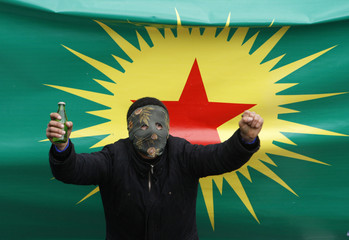 A masked demonstrator, with a banner of the outlawed Kurdistan Workers Party (PKK) in the background, marches during a protest against the High Election Board's decision in Istanbul