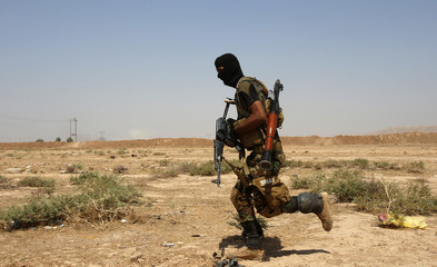 An Asaib Ahl al-Haq Shi'ite militia fighter from the south of Iraq runs during a mission to take control of the Sulaiman Pek village from Islamist State militants, in the northwest of Tikrit city