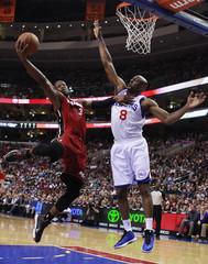 Miami Heat's Wade shoots under pressure from Philadelphia 76ers' Wilkins during NBA basketball game in Philadelphia