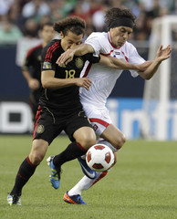 Costa Rica's Cristian Bolanos and Mexico's Andres Guardado fight for the ball in Chicago