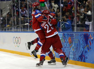 Russia's Gavrilova celebrates her goal against Germany with teammates Shokhina and Smolentseva during the third period of their women's ice hockey game at the Sochi 2014 Sochi Winter Olympics