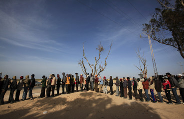 Bangladeshi evacuees line up for food at a refugee camp near the Libyan and Tunisian border crossing of Ras Jdir