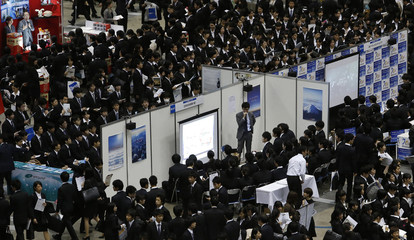 Job seekers listen to presentations at company booths during a job fair held for fresh graduates in Tokyo