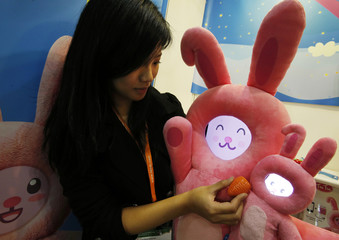 An exhibitor pretends to feed toy rabbits, with their faces powered by an iPad and an iPhone, at the Hong Kong Toys and Games Fair