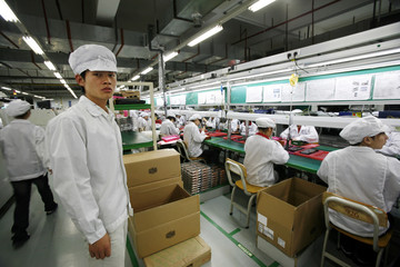 Cao Yi from Henan province poses as he works inside a Foxconn factory in the township of Longhua in the southern Guangdong province