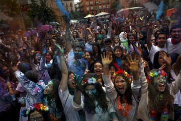 People scream as they throw coloured powder during Holi festival in Madrid