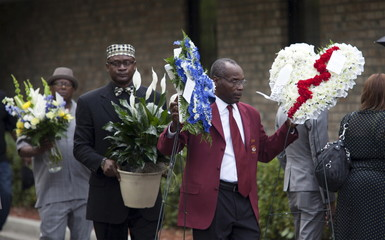 Mourners carry flowers outside the W.O.R.D. Ministry Christian Center in Summerville
