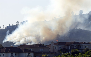 A wildfire continues to burn on the hills near San Marcos California