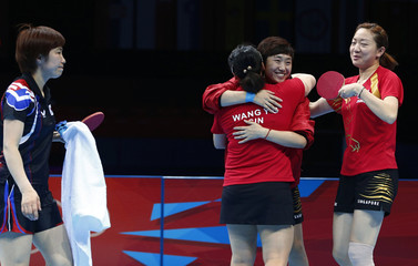 Singapore's Wang Yuegu, Feng Tian Wei and Li Jiawei celebrate after defeating South Korea in their women's team bronze medal table tennis match at the ExCel venue during the London 2012 Olympic Games