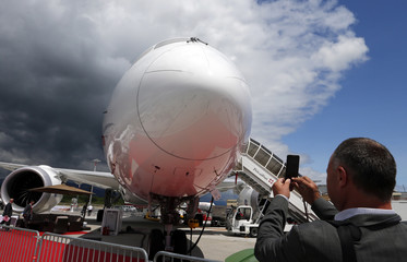 A visitor takes a picture of a Boeing Business Jet 787 aircraft during EBACE at Cointrin airport in Geneva