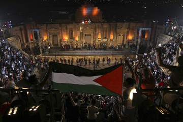 Spectators hold a Palestinian flag as they cheer Al-Ashiqeen (Lovers), a Palestinian band, at the Jerash Festival