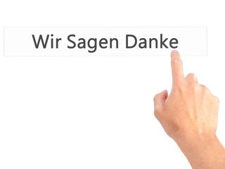 Wir Sagen Danke (We Say Thank You In German) - Hand pressing a button on blurred background concept on visual screen.