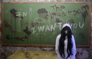 """An actor dressed as a ghost scares people entering a """"haunted school"""" during a Halloween celebration at a mall in Manila"""