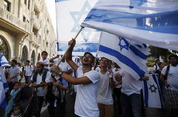 People wave Israeli flags as they take part in a parade marking Jerusalem Day, in Jerusalem