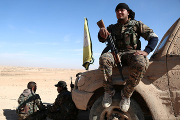 A Syrian Democratic Forces (SDF) fighter rests with his weapon on a vehicle camouflaged with mud, north of Raqqa city