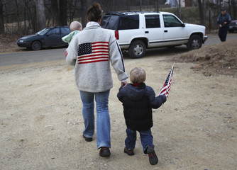 Rebecca Stuart walks with her children after voting at Loudon Town Hall in Loudon, New Hampshire