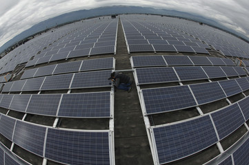 Photographer takes a picture of solar panels on the roof of the Palexpo Exhibition Center in Geneva