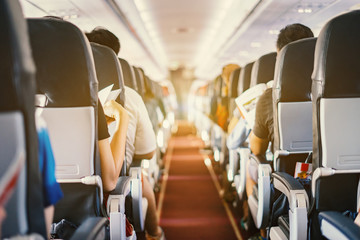 Printed kitchen splashbacks Airplane passenger seat, Interior of airplane with passengers sitting on seats and stewardess walking the aisle in background. Travel concept,vintage color,selective focus