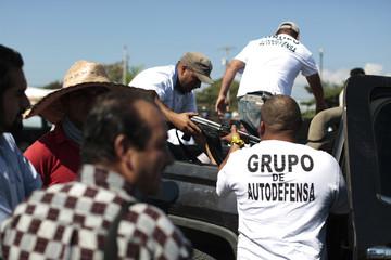 Vigilantes pass a weapon into the cabin of a pick up truck in Nueva Italia