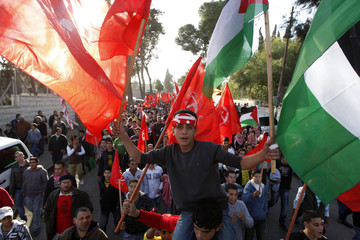 A Palestinian man holds flags of the PFLP during a rally organized by it to celebrate the 43rd anniversary of its founding in the West Bank city of Ramallah