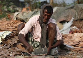 A labourer cuts scrap leather at a factory in Kolkata