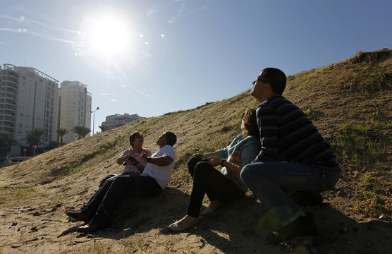 Israeli people look up at the sky with smoke trails from an Iron Dome interceptor rocket and try to take cover as a siren sounds warning of incoming rockets in Ashdod