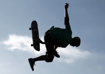 A skate boarder spins his board between his feet as he sails off the top of a half pipe skate ramp in Encinitas, California