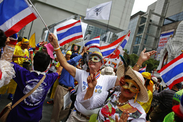 Anti-government protesters wearing masks wave Thai flags during a protest in Bangkok