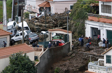 People dry and clean streets and houses in downtown Funchal as damaged vehicles lie above debris after heavy flooding on Madeira island