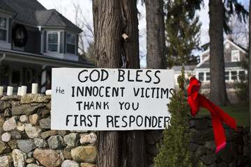 "Sign reading ""God Bless The Innocent Victims, Thank You First Responders"" is seen in Sandy Hook"