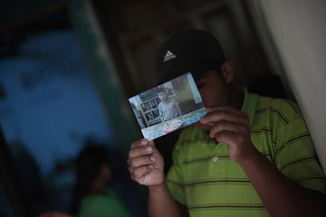 Wilson Oswaldo Coi Cal, a brother of 13-year-old Juan Armando Coy Cal who was killed by a man in a classroom at a primary school, shows a picture of his brother in his home in Tactic