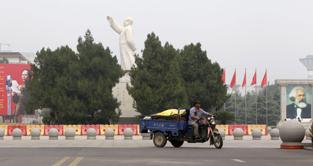A resident drives a motor tricycle past a statue of the late Chairman Mao Zedong next to a portrait of German philosopher Karl Marx at Dong Fang Hong Square in Nanjie village of Luohe city