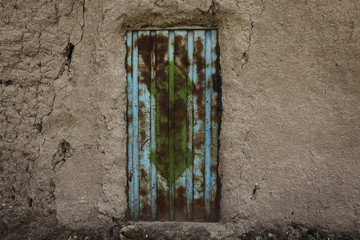 A rusted metal door marks the entrance to a mud compound at the village of Kunkak in southern Afghanistan's Helmand province