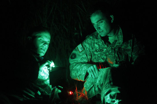 """US Army soldiers consult a map before hiking to the final review board station while on a 24 hour Cavalry """"Spur Ride"""" for members of the US Army's 6th Squadron, 6th Cavalry Regiment in Fort Drum, New York"""
