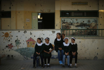Palestinian students sit inside their damaged school on the first day of the new school year in the east of Gaza City