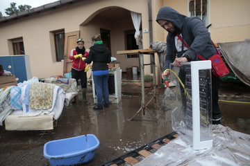 People wash their belongings outside a flooded home after extreme rainfall due to Cyclone Cleopatra in Olbia on Sardinia island