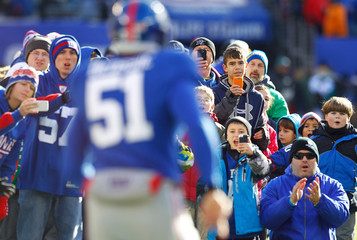 Students and families from Newtown, Connecticut's Sandy Hook Elementary School applaud as New York Giants Zak DeOssie runs onto the field before their NFL football game against the Philadelphia Eagles in East Rutherford