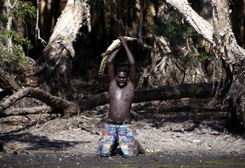 Australian Aboriginal hunter Marcus Gaykamangu lifts a baby crocodile above his head after capturing it at a billabong near the 'out station' of Yathalamarra located on the outksirts of the community of Ramingining in East Arnhem Land